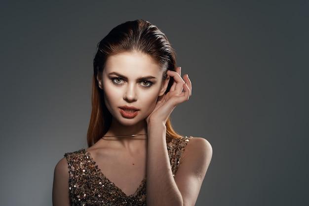 Wesoła kobieta w złotej sukience biżuteria kolczyki moda glamour. zdjęcie wysokiej jakości