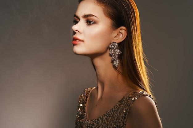 Wesoła kobieta w złotej sukience biżuteria kolczyki moda glamour