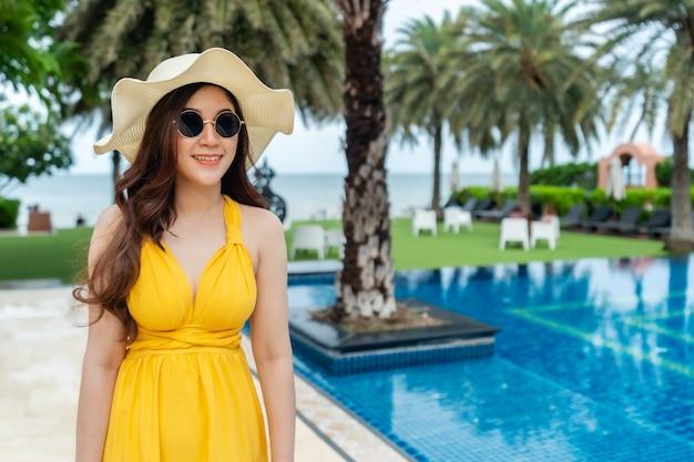Wesoła kobieta w żółtej sukience w pobliżu basenu i plaży