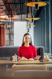 Wesoła kobieta wesoła piękna kobieta z czerwonymi ustami je pyszne śniadanie w restauracji