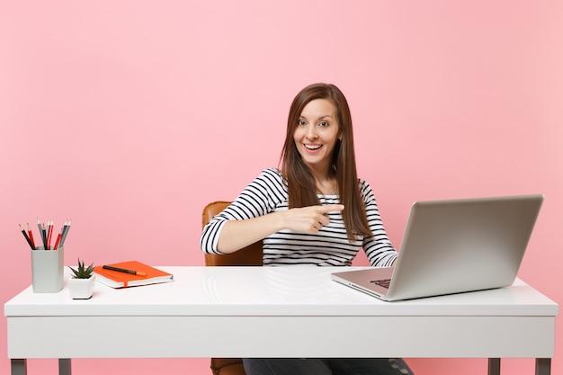 Wesoła kobieta wskazuje palcem wskazującym na współczesnym laptopie pc podczas pracy, siedzi przy biurku w biurze