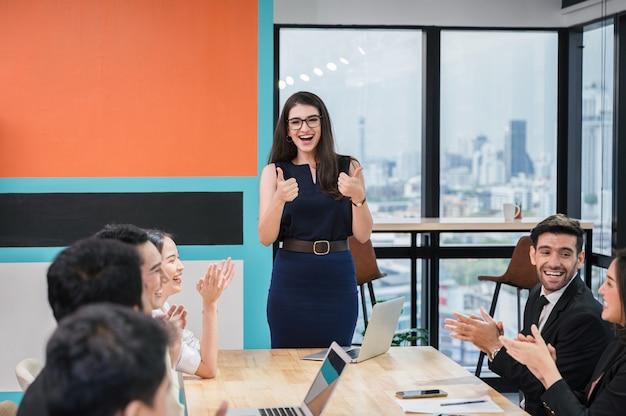 Wesoła kobieta wykonawcza pokazująca kciuki do góry z wieloetnicznymi kolegami z gratulacjami podczas spotkania w nowoczesnym biurze