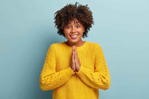 Wesoła kobieta z afro pozowanie w różowym swetrze