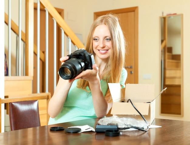 Wesoła kobieta z blond włosy rozpakowywanie nowego aparatu cyfrowego w domu