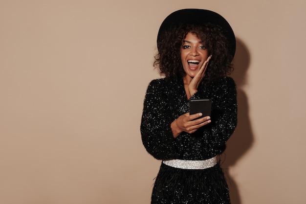 Wesoła kobieta z brunetką fryzurę w modny kapelusz i czarny sweter z błyszczącym paskiem patrząc w kamerę i trzymając smartfon na beżowej ścianie...