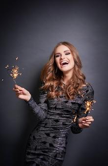 Wesoła kobieta z brylant śmiejąc się w szarej ścianie