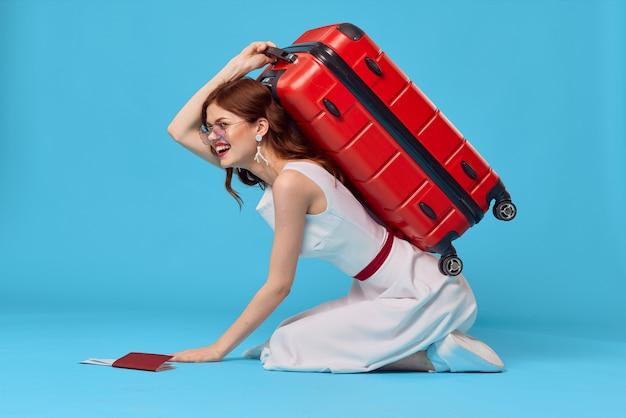 Wesoła kobieta z czerwoną walizką siedzi na podłodze emocje na białym tle