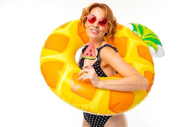 Wesoła kobieta z jasnymi rudymi włosami w stroju kąpielowym