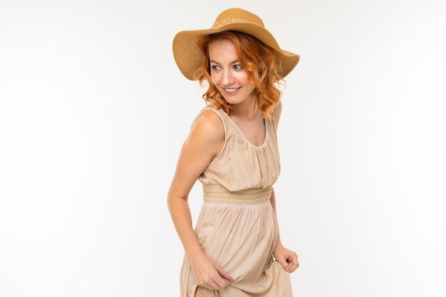 Wesoła kobieta z jasnymi rudymi włosami w uśmiechach pięknej sukni, zdjęcie na białym tle