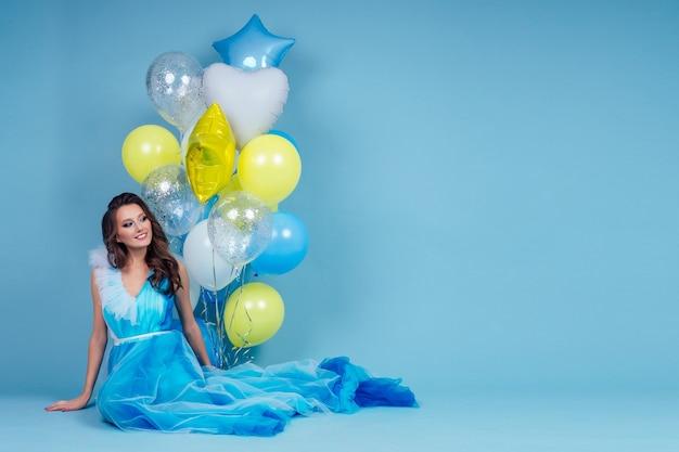 Wesoła kobieta z niebieskimi, żółtymi i białymi balonami z helem siedzi i bawi się na wakacjach na imprezie na niebieskim tle studio.dziewczyna w długiej sukience pozowanie makijaż i fryzura idealna skóra
