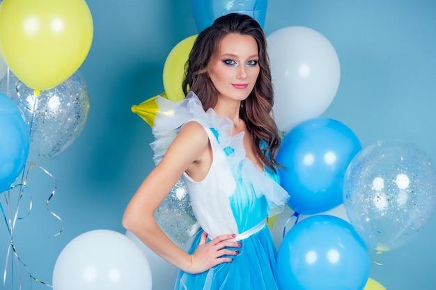 Wesoła kobieta z niebieskimi, żółtymi i białymi balonami z helem tańczy i bawi się na wakacjach na imprezie na niebieskim tle studio.dziewczyna w długiej sukience pozuje makijaż i fryzurę idealną skórę