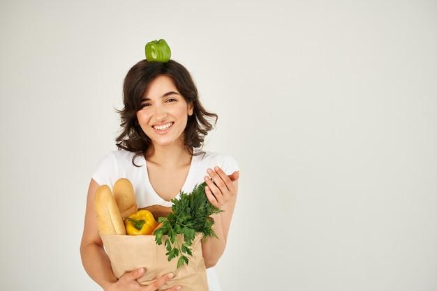 Wesoła kobieta z paczką artykułów spożywczych zakupy w supermarkecie ze zdrową żywnością