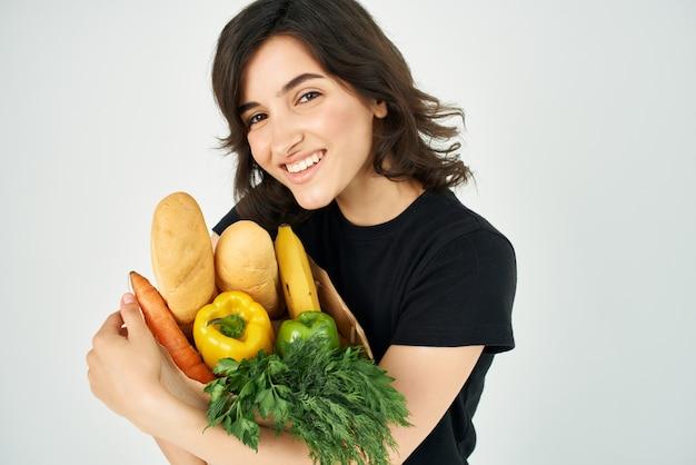 Wesoła kobieta z paczką spożywczy dostawy warzyw. zdjęcie wysokiej jakości