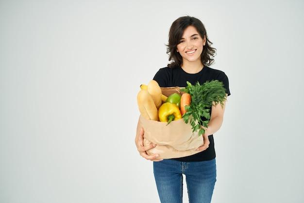 Wesoła kobieta z paczką warzyw zdrowa żywność jasne tło