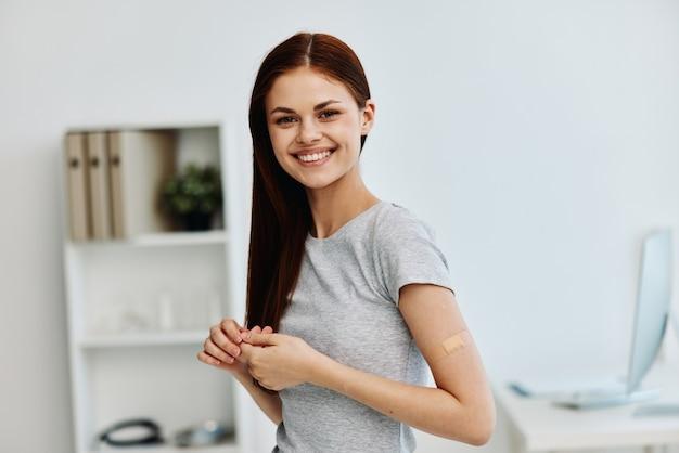 Wesoła kobieta z plastrem na ramieniu paszport szczepionkowy ochrona immunologiczna