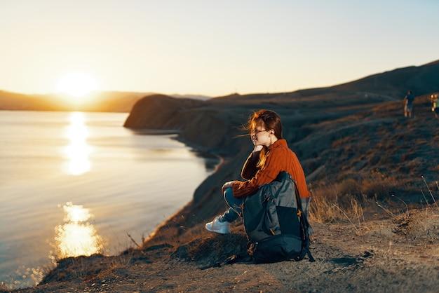 Wesoła kobieta z plecakiem w górach podróżuje krajobraz wolności