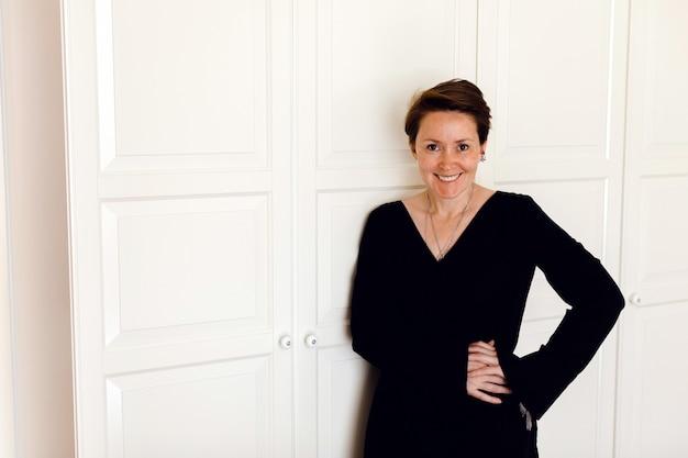 Wesoła kobieta z rękami na talii przed białymi drzwiami szafy