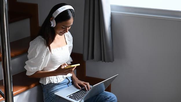 Wesoła kobieta z słuchawki pracuje online na laptopie i przy użyciu smartfona, siedząc na klatce schodowej.
