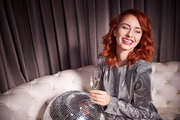 Wesoła kobieta z szampanem i kulą dyskotekową w klubie nocnym