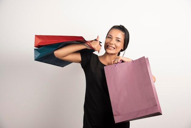 Wesoła kobieta z torby na zakupy na białej ścianie.