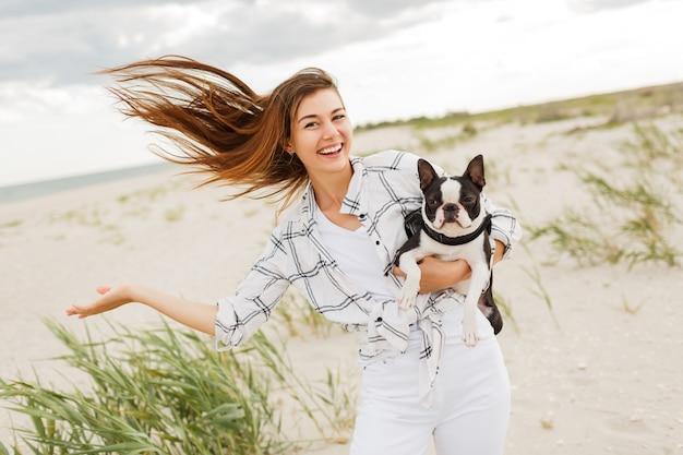 Wesoła kobieta z uroczym psem boston terrier ciesząc się weekendem w pobliżu oceanu. kobieta tańczy i dobrze się bawi.