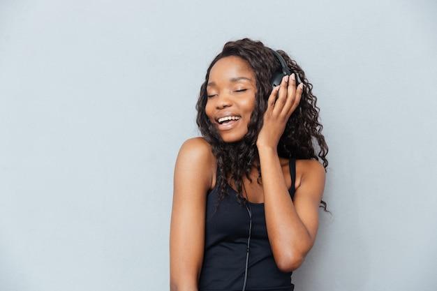 Wesoła kobieta z zamkniętymi oczami słuchająca muzyki w słuchawkach na szarej ścianie