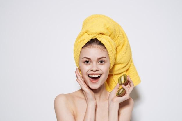 Wesoła kobieta z żółtym ręcznikiem na głowie z kiwi