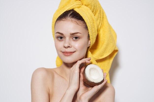 Wesoła kobieta z żółtym ręcznikiem na głowie z kokosem