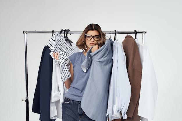 Wesoła kobieta zakupoholiczka wybierająca ubrania na zakupy w sklepie jasnym tle