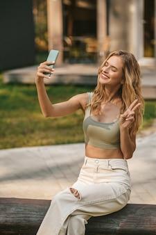 Wesoła kobieta ze smartfonem pokazująca palcami znak wolności