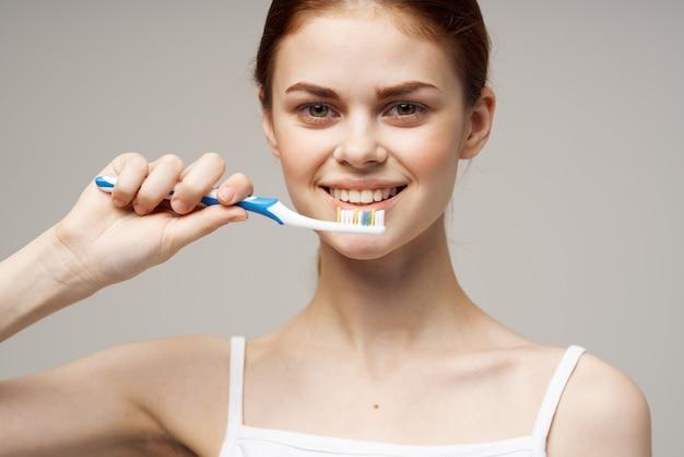 Wesoła kobieta ze szczoteczką do zębów w ręku rano higiena na białym tle