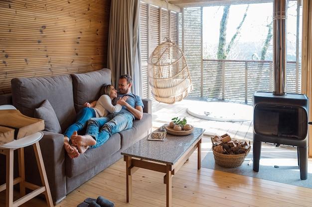 Wesoła, kochająca para w ubranie, przytulanie i całowanie, odpoczywając razem na kanapie w stylowym salonie z drewnianym wnętrzem