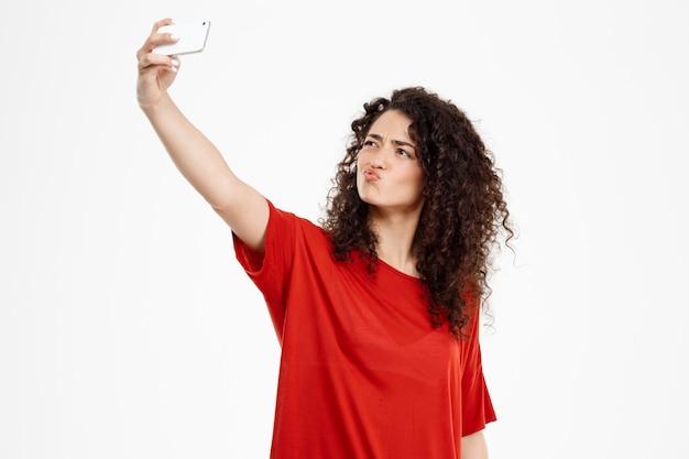 Wesoła kręcona dziewczyna zrobić selfie
