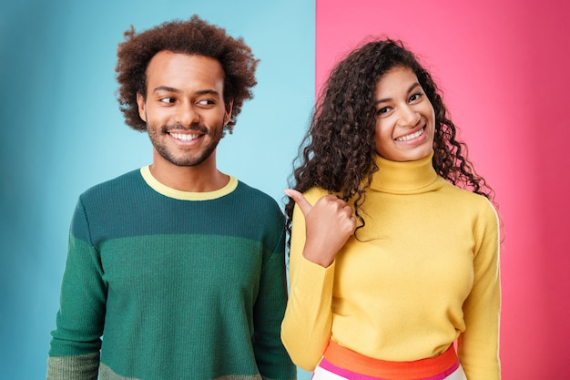 Wesoła, kręcona młoda kobieta stojąca i wskazująca na swojego chłopaka na kolorowym tle