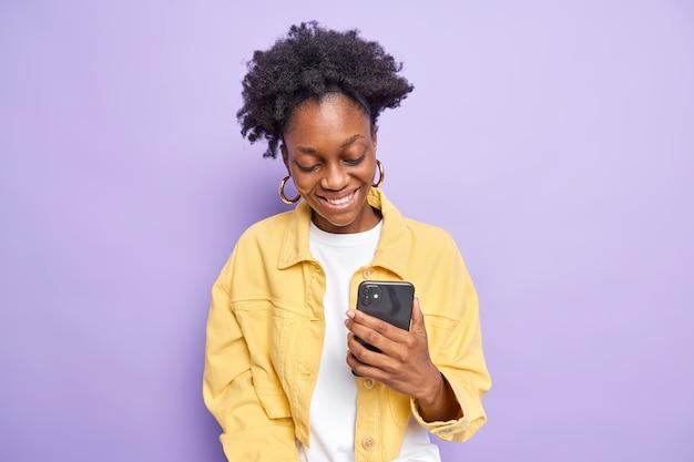Wesoła, kręcona nastolatka używa telefonu komórkowego do robienia zakupów online lub wysyłania wiadomości tekstowych, uśmiecha się szczęśliwie, ma wyraz zadowolenia