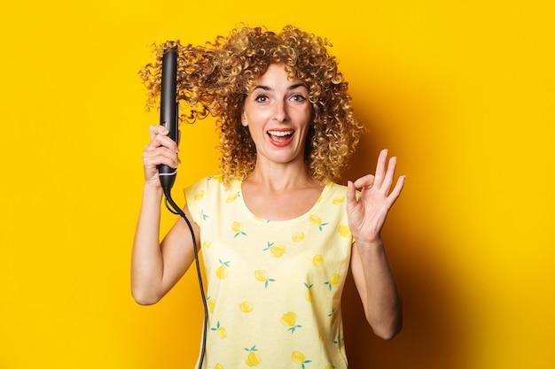 Wesoła, kręcone, młoda kobieta prostuje prostownicę do włosów na żółtym tle.