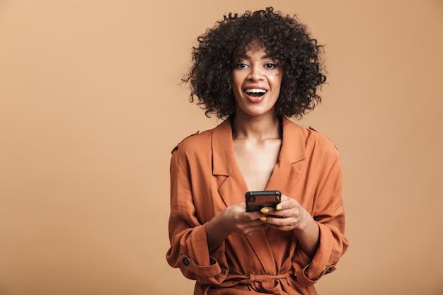 Wesoła, ładna afrykańska kobieta trzymająca smartfon i patrząca bezpośrednio na brązowym tle