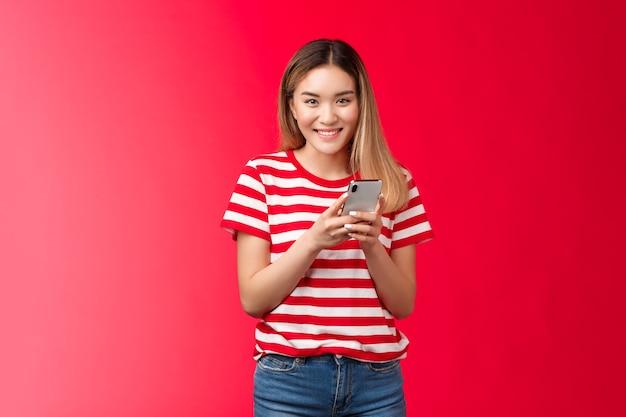 Wesoła ładna azjatycka blond dziewczyna chichocze uśmiechnięta ząbka czuje się szczęśliwa trzymając smartfon czytaj przyjaciel f...