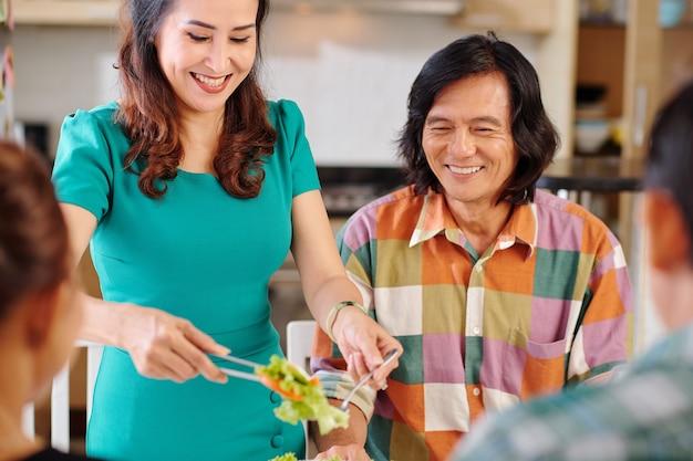 Wesoła, ładna dojrzała azjatka wkłada sałatkę jarzynową do talerza męża podczas świątecznej kolacji w domu