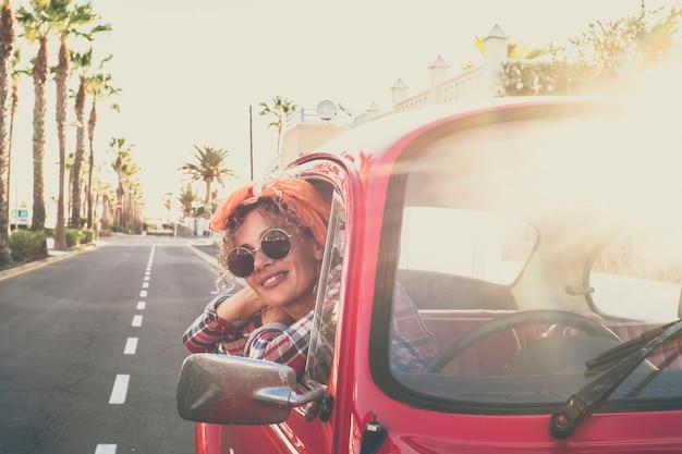 Wesoła, ładna, dorosła, młoda kaukaska kobieta uśmiecha się i cieszy podróżą stojąc na zewnątrz czerwonego samochodu stary pojazd patrzący - modne kobiety w okularach przeciwsłonecznych i kolorowe ubrania - droga w tle
