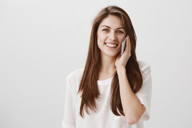 Wesoła ładna dziewczyna rozmawia przez telefon i uśmiecha się