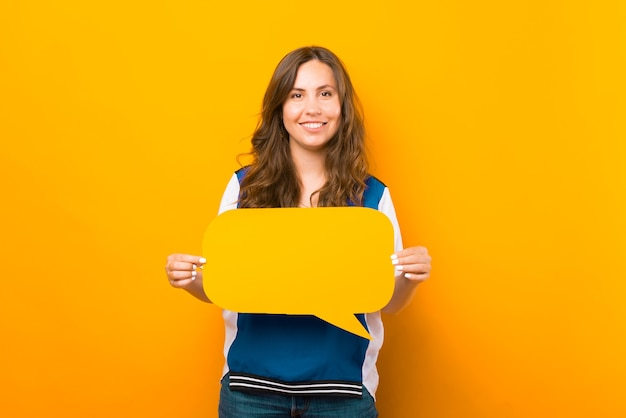 Wesoła ładna dziewczyna trzyma żółtą bańkę mowy.