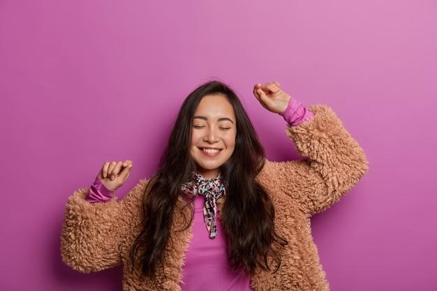 Wesoła ładna dziewczyna z podniesionymi rękami, radośnie tańczy w nowym stroju, zamyka oczy z przyjemności, porusza się do ulubionej muzyki