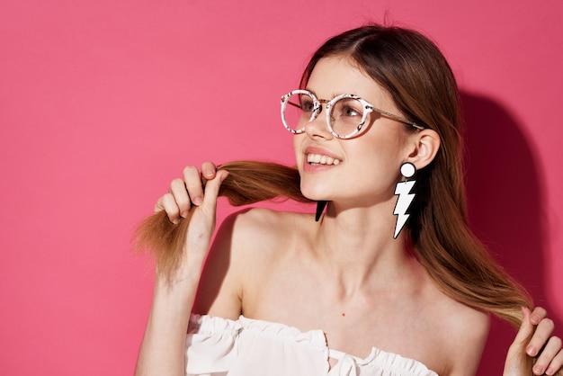 Wesoła ładna kobieta kolczyki biżuteria atrakcyjny wygląd moda blask różowy tło. wysokiej jakości zdjęcie
