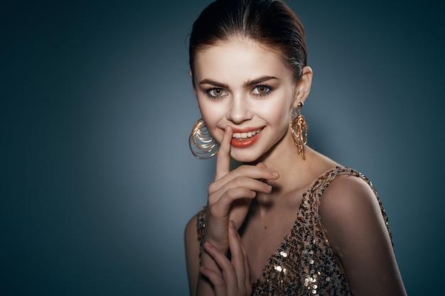 Wesoła ładna kobieta na złotej sukience jasny makijaż studio luksus