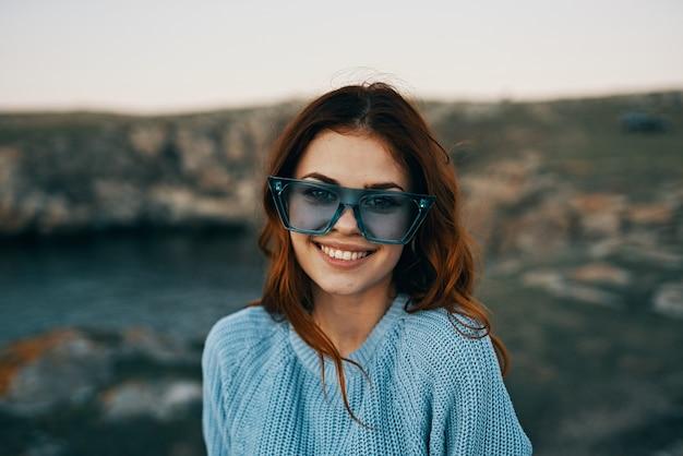 Wesoła ładna kobieta w niebieskich okularach na zewnątrz podróży luksusu