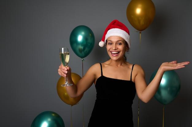Wesoła ładna kobieta w santa hat raduje się i bawi się na przyjęciu bożonarodzeniowym trzyma flet szampana i kopiuje miejsce na dłoni do góry, na białym tle na szarym tle z błyszczącymi złotymi i zielonymi balonami