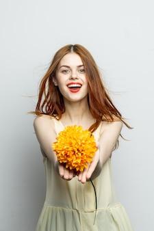 Wesoła ładna kobieta z dużym żółtym kwiatem w dłoniach emocje czerwone usta zabawa urok.