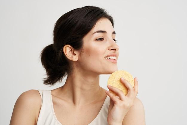 Wesoła ładna kobieta z gąbką w dłoniach kosmetyki do pielęgnacji skóry kolor tła jasnym tle. wysokiej jakości zdjęcie
