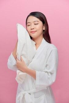 Wesoła ładna kobieta ze zdrową skórą osusza twarz białym miękkim bawełnianym ręcznikiem po porannej higienie przed kamerą